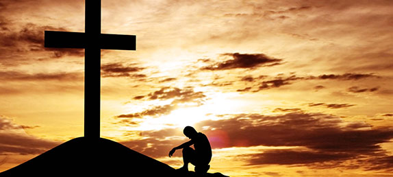 A person kneeling in front of a cross at sunset. Salvation can only be attained through Jesus' crucifixion and Resurrection.