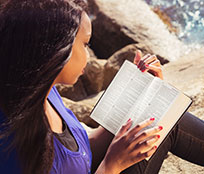 A woman by the water reading and studying passages from different translations of the Bible.
