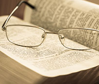Eyeglasses on top of a Bible where study is spontaneous and flexible when you can search passages in different translations.